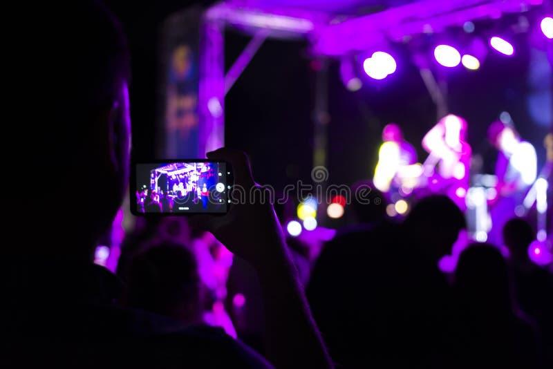 Widz strzela koncert na smartphone Jaskrawa scena z światłami Ostro?? zamazuje zdjęcie stock
