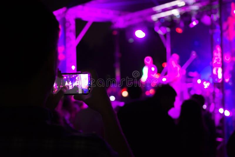 Widz strzela rockowego koncert na smartphone Jaskrawa scena z światłami Ostro?? zamazuje obrazy stock