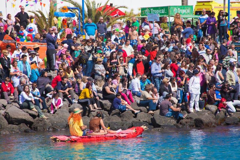 Widzowie oglądają brać woda w corocznym Regata De Achipencos w Puerto Del Rosario gdy uczestnicy zdjęcia stock