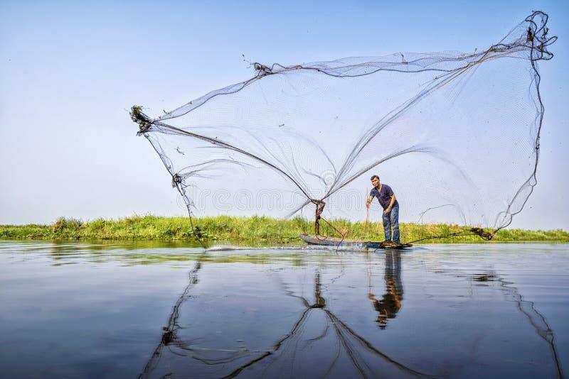 Wieśniacy ciskają ryby Rybak sieci rybackie Miotanie sieć rybacka podczas ranku na drewnianej łodzi, Tajlandia zdjęcia royalty free
