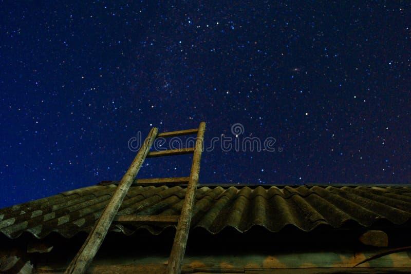 wieśniacy Stary drewniany drabinowy opierać przeciw stajni z łupkowym dachem w nocy gwiazdy niebie Schody prowadzi fotografia stock