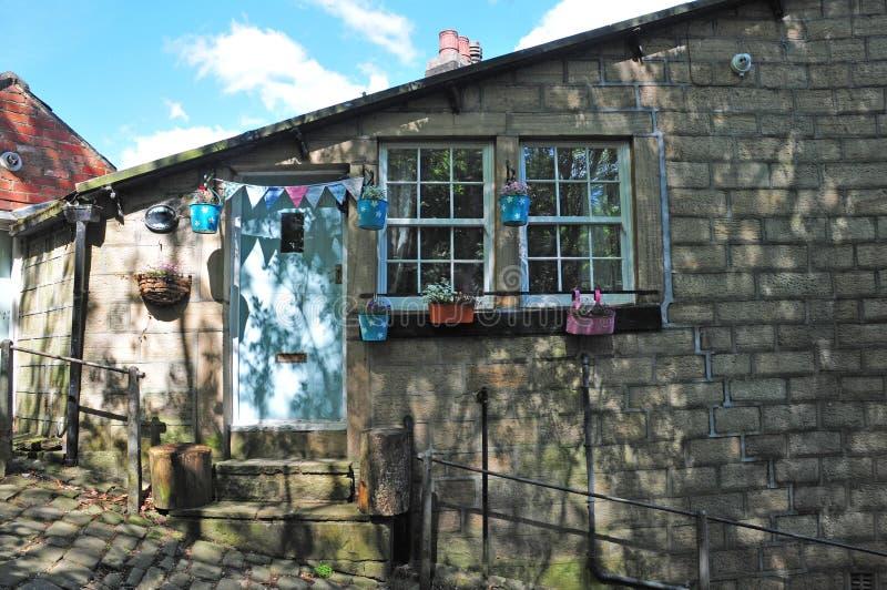 Wieśniak kamienna chałupa na stromym pochylaniu brukował ulicę pośrodku hebden most i heptonstall w Yorkshire z kolorowymi kwiató obrazy stock
