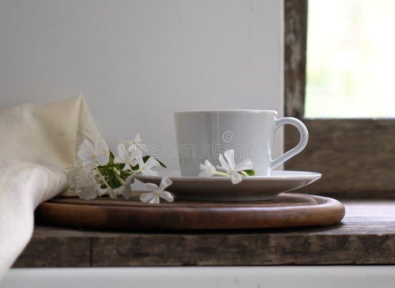 wieśniak nadal życia filiżanka herbata na nadokiennym parapecie białym floksie i kwitnie Rocznika drewniany tło Zakończenie zdjęcie royalty free