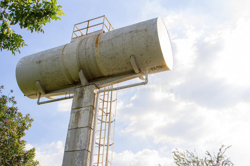 Wieża ciśnień przeciw staremu białemu zbiornikowi i niebieskiemu niebu obraz royalty free