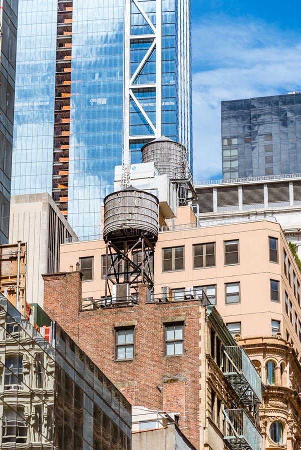 Wieże ciśnień na dachu starzy budynki przeciw nowożytnemu skyscrap obraz royalty free