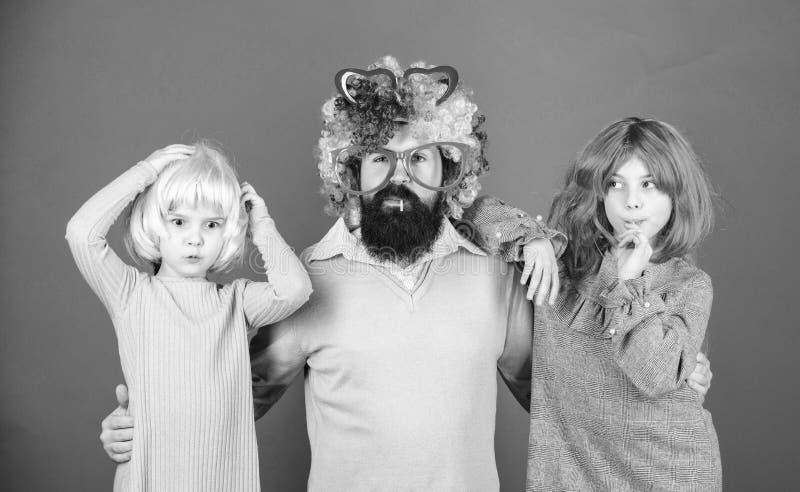 Wie Ihr Vater verr?ckt ist B?rtiger Vater des Mannes und Kinderm?dchen tragen violetten Hintergrund der bunten Per?cke Freundlich stockfotos