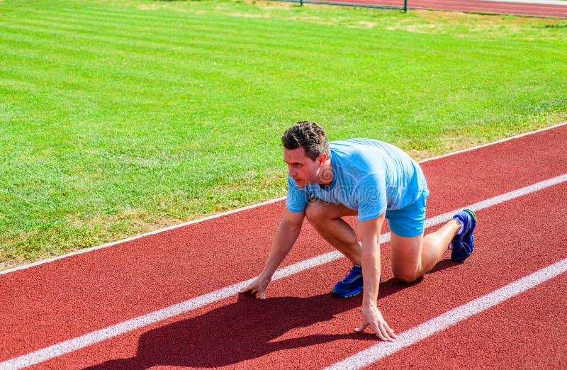 Wie man beginnt zu laufen Sportspitzen vom Berufsläufer Positionsstadionsweg des Mannathletenläuferstands niedriger Anfangs lizenzfreies stockfoto