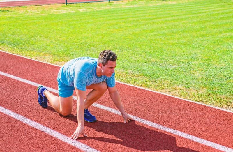 Wie man beginnt zu laufen Sportspitzen vom Berufsläufer Positionsstadionsweg des Mannathletenläuferstands niedriger Anfangs lizenzfreie stockfotografie