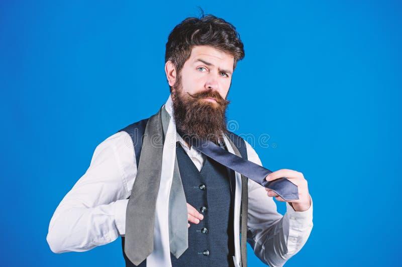 Wie man Krawatte mit Hemd und Anzug zusammenbringt B?rtiger Hippie-Griff des Mannes wenige Krawatten auf blauem Hintergrund Kerl  stockfotografie