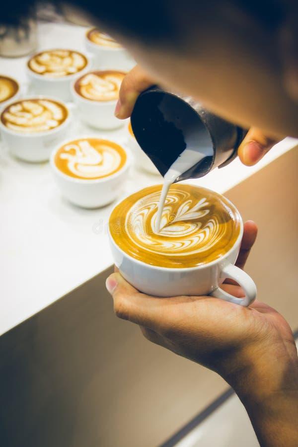 Wie man Lattekunstkaffee durch barista macht lizenzfreie stockbilder