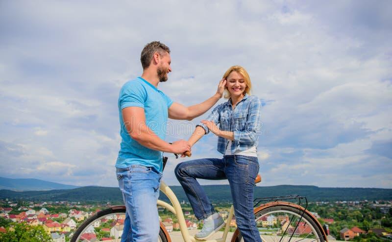Wie man Mädchen beim Reiten des Fahrrades trifft Mann mit Bart und werfen blonde Dame auf erstem Datum Mädchen aufheben Paare tre stockfotografie