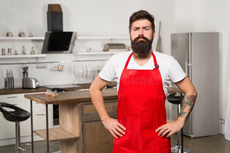Wie man zu Hause kochen zu Gewohnheit macht Schutzblechstand des bärtigen Hippies des Mannes roter in der Küche Küchenmöbelgeschä stockbild