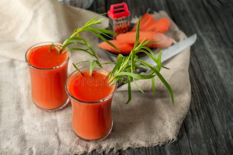?wie?y domowej roboty marchwiany sok w dwa szklanej fili?anki Z marchewk? i bia?ymi kwiatami obraz stock