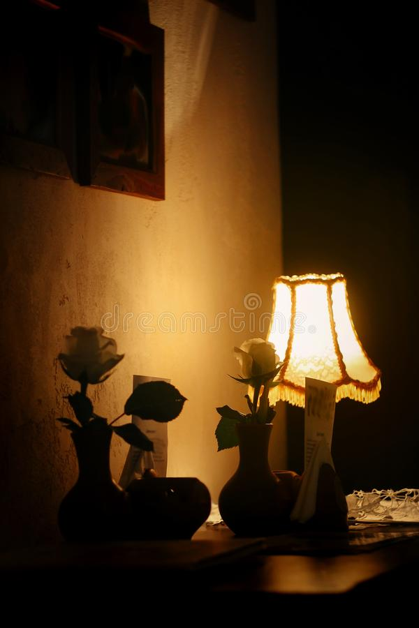 Wieczór lampa z różami i grże światło w rocznika pokoju kawiarnia obraz stock