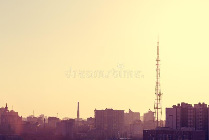 Wieczór pejzaż miejski w kolorów żółtych brzmieniach: TV góruje, domy, ćwiartki, wysoki buildin fotografia royalty free