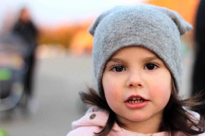 Wieczór portret piękna mała dziewczynka w kapeluszu i żakiet na tle miastowy krajobraz w zmierzchu zaświecamy zdjęcia royalty free