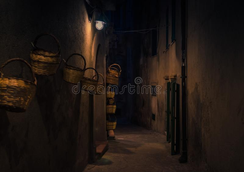 Wieczór ulica z jaskrawymi lampionów koszami na ścianie, Tropea, Ita obraz stock