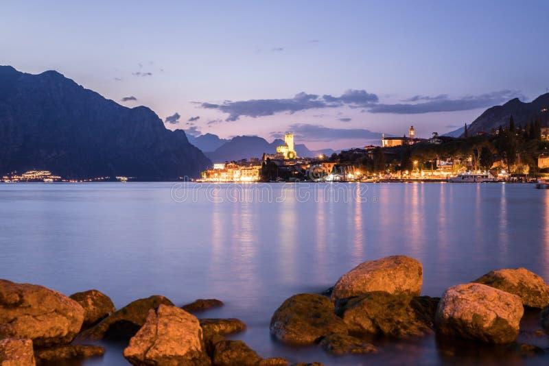 Wiecz?r scena przy Lago Di Garda: Jezioro, ska?y i wioska, fotografia stock