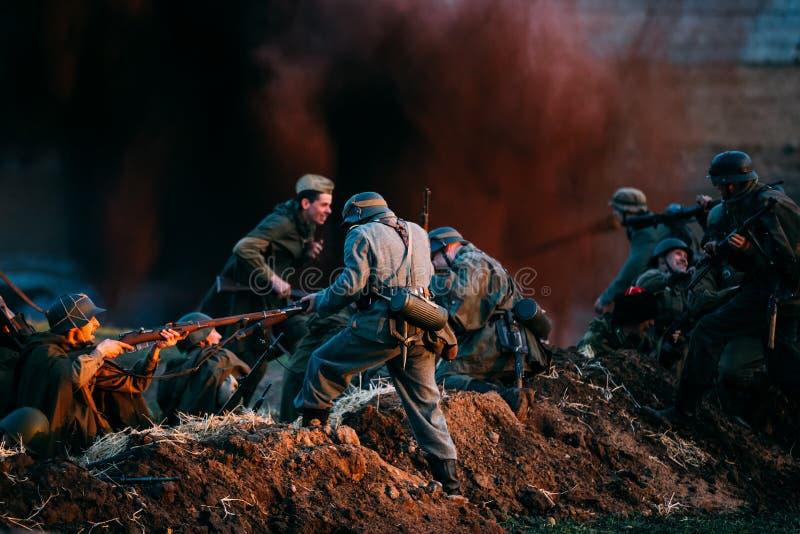 Wieder--enactors gekleidet als Deutscher Wehrmacht-Infanterie-Soldaten und russisches sowjetisches Spiel des Soldat-Zweiten Weltk stockbilder