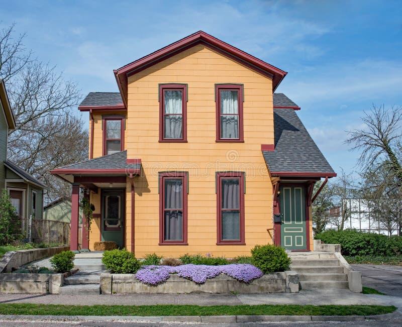 Wieder hergestelltes orange Duplexhaus mit purpurroter Flammenblume lizenzfreie stockfotografie