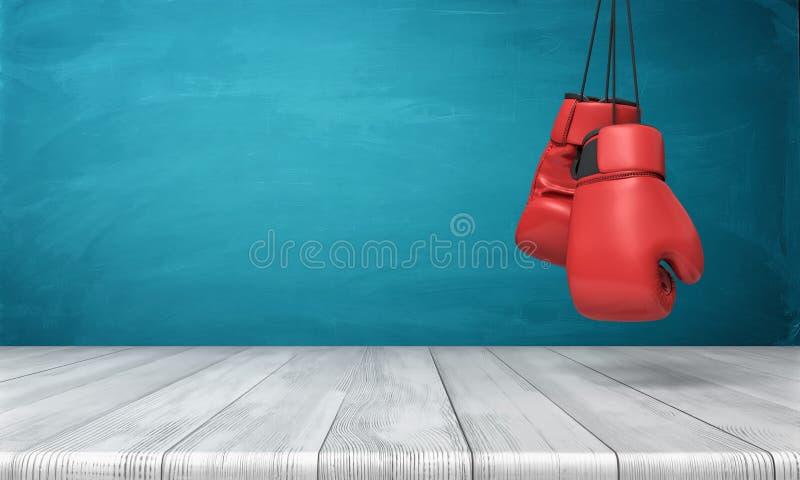 Wiedergabe 3d von zwei roten Boxhandschuhen, die über einem hölzernen Schreibtisch vor einem blauen Tafelhintergrund hängen lizenzfreies stockbild