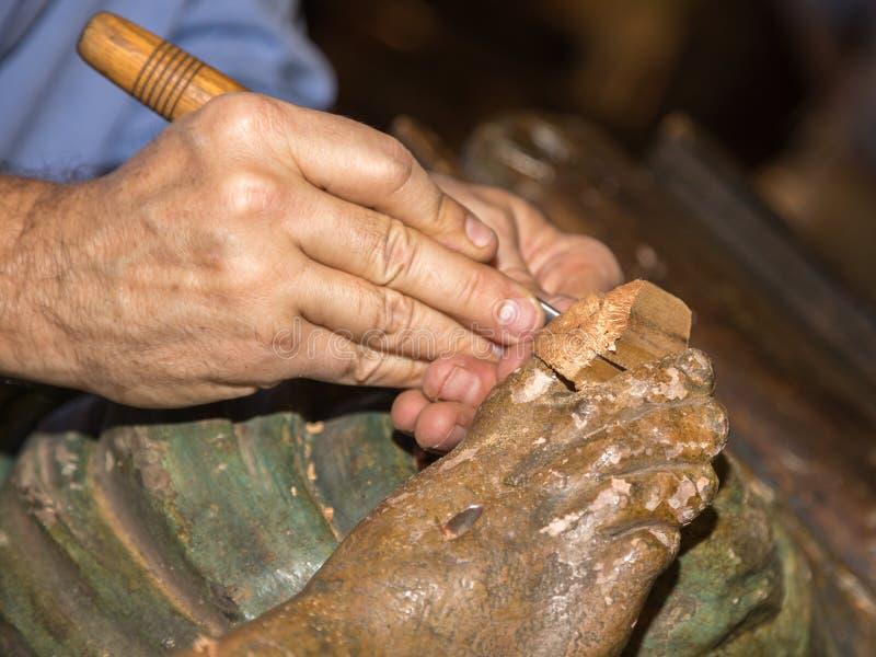 Wiederherstellung der hölzernen Skulptur: Nahaufnahme des Stärkungsmittels arbeitend an Reli stockfoto