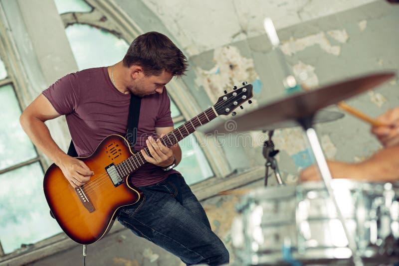 Wiederholung der Rockmusikband E-Gitarren-Spieler und Schlagzeuger hinter dem Trommelsatz stockbild