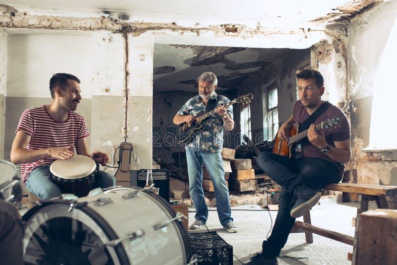 Wiederholung der Rockmusikband E-Gitarren-Spieler und Schlagzeuger hinter dem Trommelsatz stockfotografie