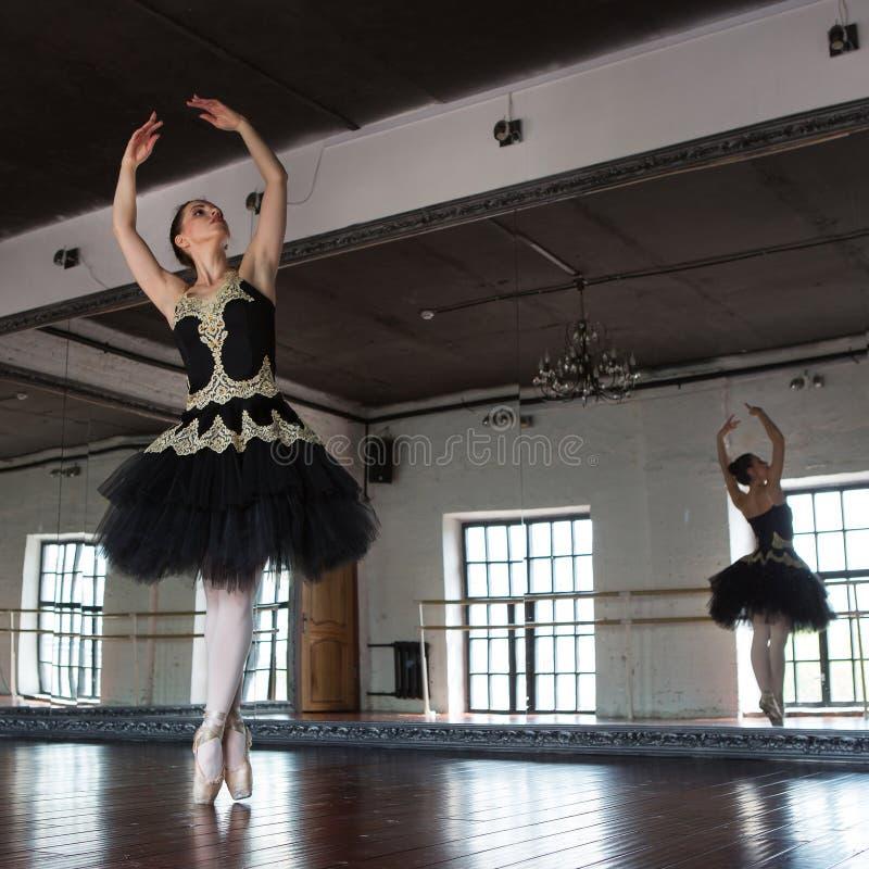 Wiederholungsballerina in der Halle Wei?e W?nde, dunkler Bretterboden, dunkle Decke, gro?e Spiegel Die Reflexion der Ballerina he stockfotografie