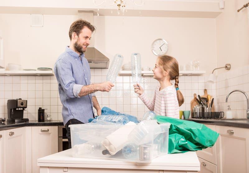Wiederverwertung - Familie, die Spaß beim Sortieren des Abfalls hat stockbilder