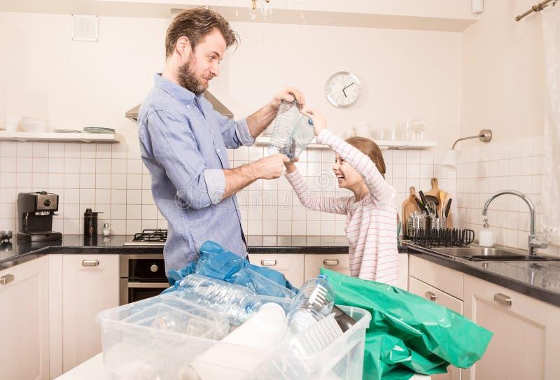 Wiederverwertung - Familie, die Spaß beim Sortieren des Abfalls hat lizenzfreie stockfotografie