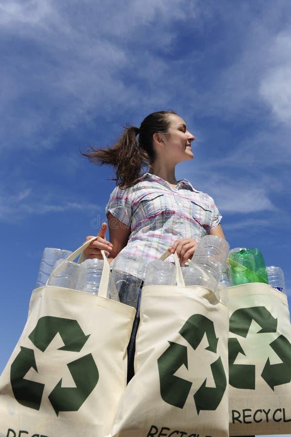 Wiederverwertung: Frauenholdingbeutel mit Plastikflaschen lizenzfreie stockfotos