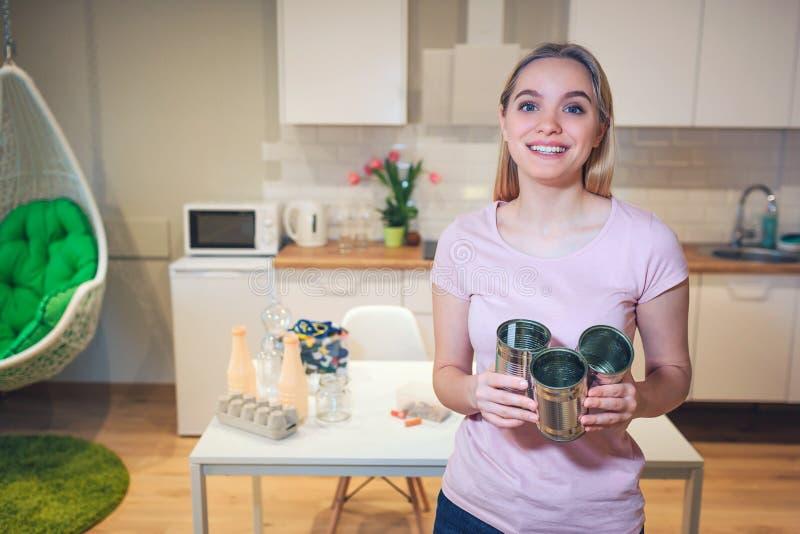 wiederverwertung Junge lächelnde Frau, die Metallblechdosen für Wiederverwendung auf Küchenhintergrund hält lizenzfreies stockfoto