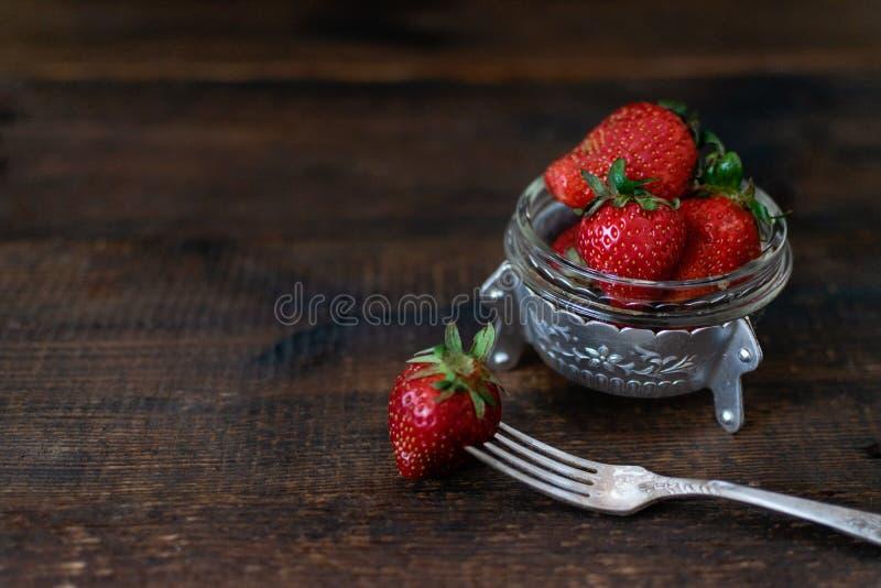 Wiejska świeża organicznie truskawka w metalu pucharze i rozwidlenie na ciemnym drewnianym wieśniaka stole Czerwona surowa truska fotografia stock