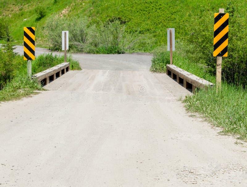 Wiejska droga gruntowa krzyżuje wąskiego drewnianego most zdjęcie stock