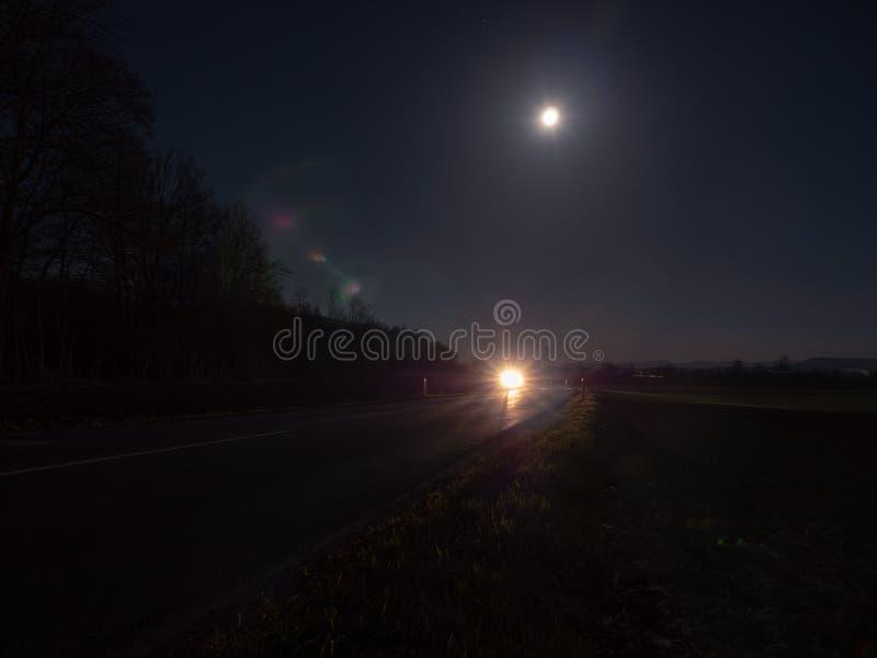 Wiejska Droga Iluminująca reflektorami Zbliża się samochód obraz royalty free