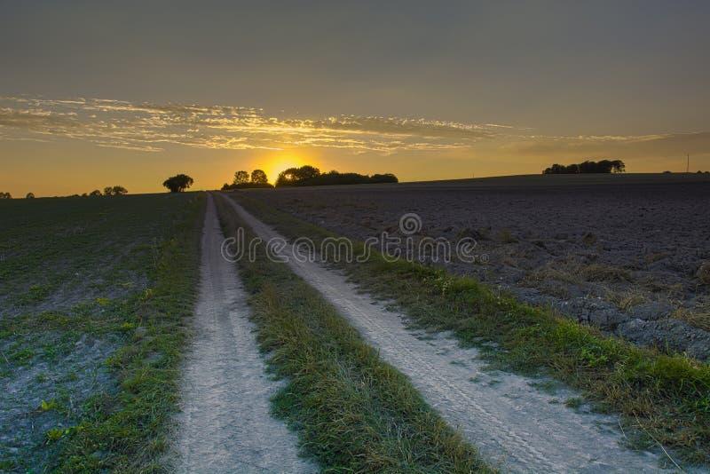 Wiejska droga, pole, wieczór niebo i zmierzch orzący, zdjęcia royalty free
