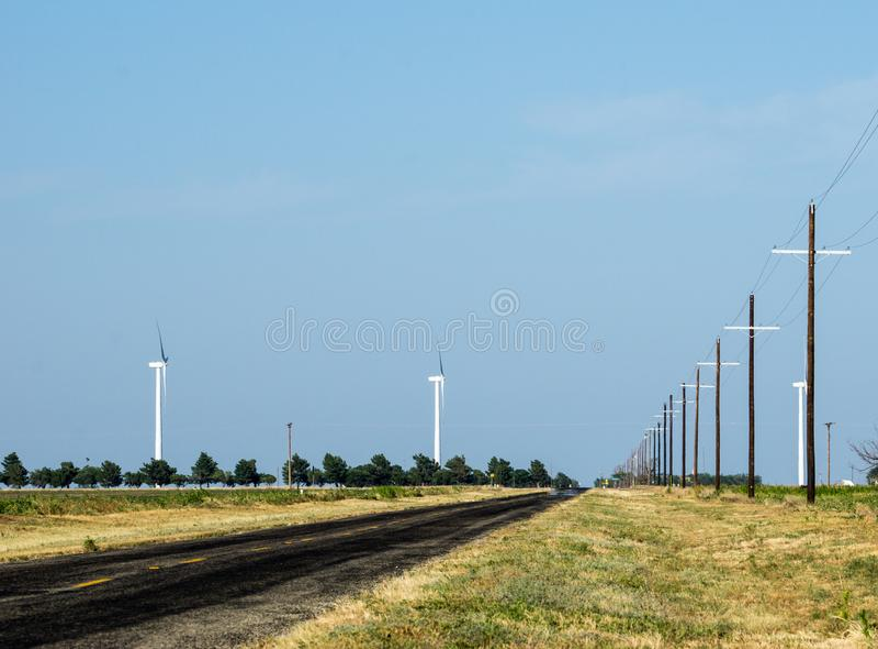Wiejska droga w pustej Teksas prerii z liniami energetycznymi i silnikami wiatrowymi za zdjęcia stock