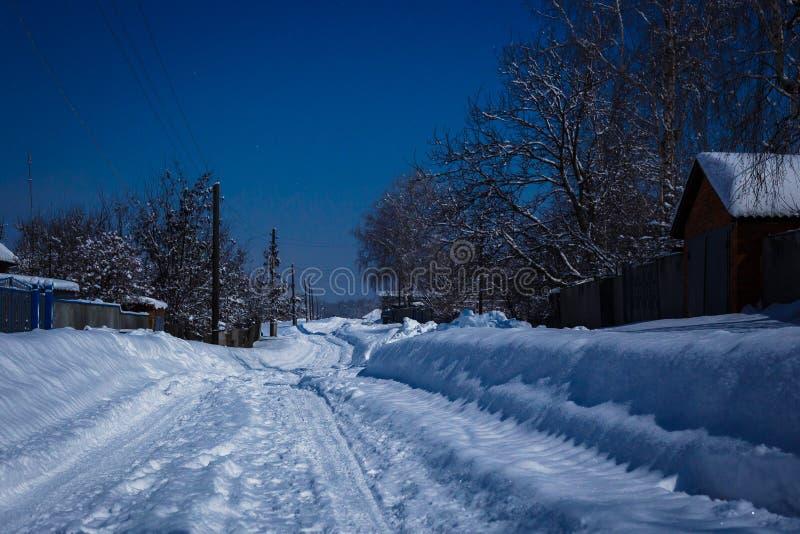 Wiejska droga w snowdrift zaświecał blaskiem księżyca przy nocą obrazy stock