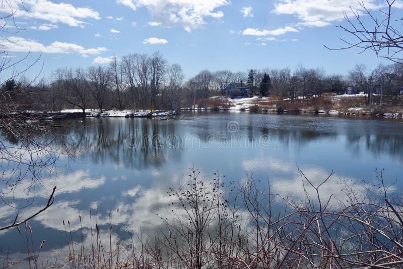 Wiejska rzeka w wczesnej wiośnie w Maine z śniegiem, chmury, nadzy drzewa, zdjęcia royalty free