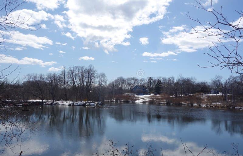 Wiejska rzeka w wczesnej wiośnie w Maine z śniegiem, chmury, nadzy drzewa, obrazy royalty free