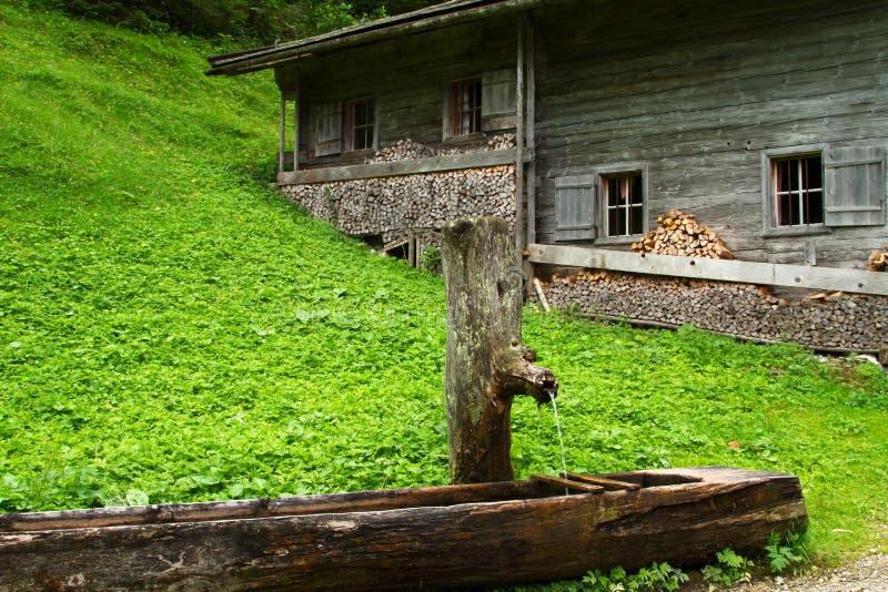 Wiejska sceneria z drewnianym wodnym well i starą wysokogórską budą blisko Falzthurnalm Achensee Jeziorny teren, Austria, Tirol obraz stock