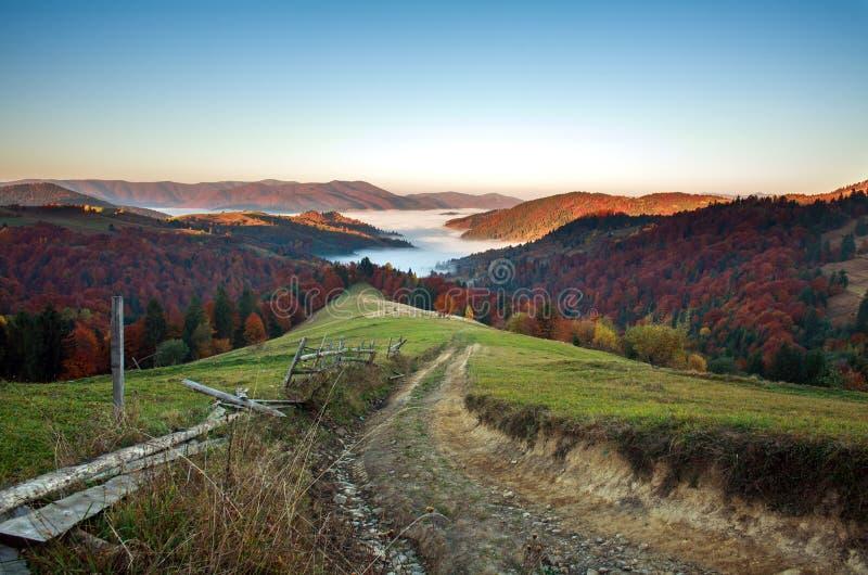 Wiejski drogowy ślad w jesieni górach w mgle przy wschodem słońca obrazy royalty free