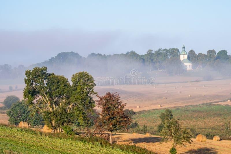 Wiejski krajobraz i starego kraju ko?ci?? w mgle zdjęcie royalty free