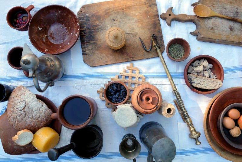 Wiejski posiłek antykwarscy naczynia, rocznik waży outdoors i prości nieociosani foods na białym tablecloth, odgórny widok obraz stock