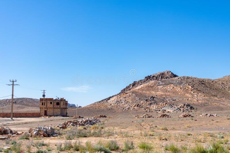 Wiejski Skalisty krajobraz z Stronniczo Budującym domem i wzgórza w Maroko fotografia royalty free