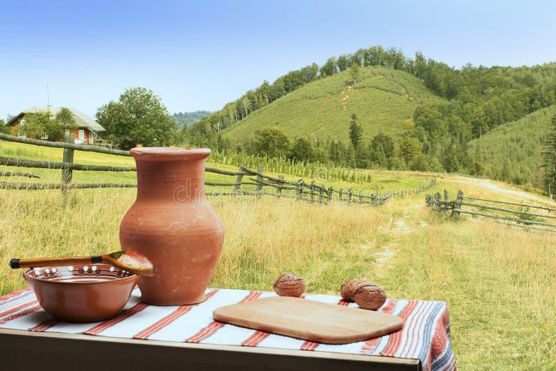 Wiejski stół z glinianymi ceramicznymi naczyniami i płótno z tradycyjnymi ukraińskimi wzorami fotografia stock