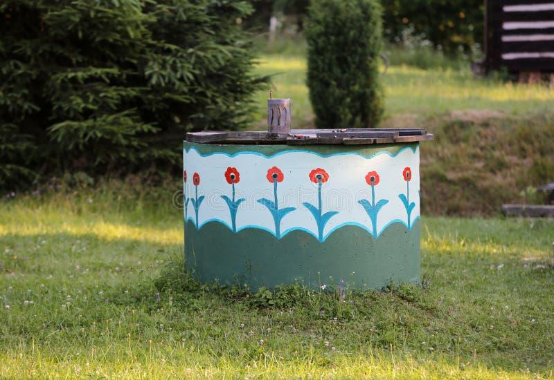 Wiejski well dekorujący z malującymi kwiatami fotografia royalty free