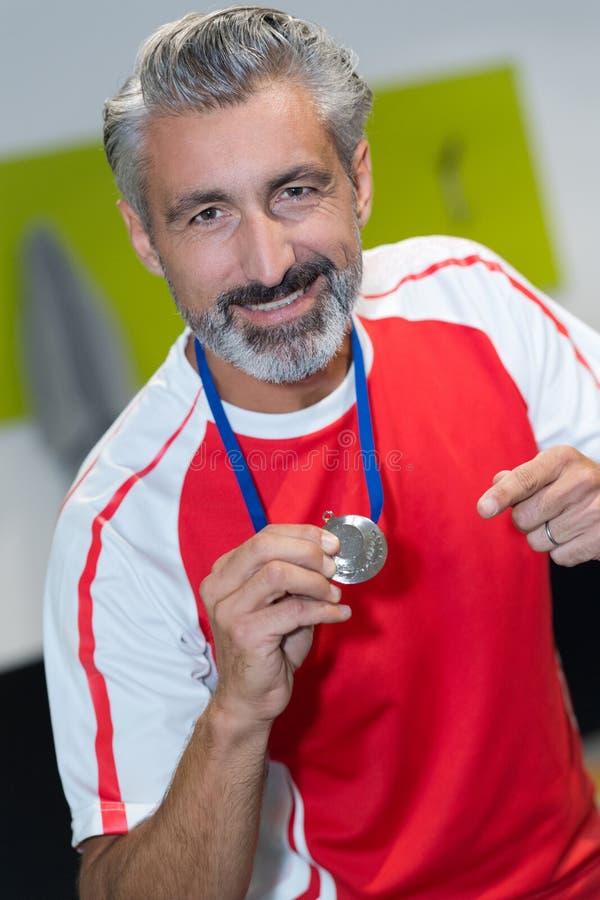 Wiek średni atlety konkurent pokazuje wygranego medal obrazy royalty free