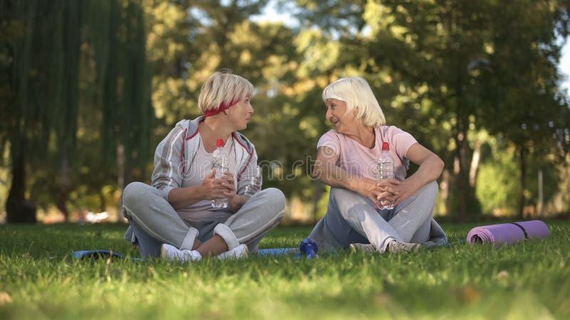 Wiek średni kobieta i jej matka opowiada po robić ćwiczeniom i joga w parku obrazy stock